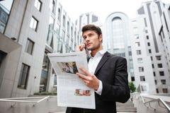 Σκεπτικός νέος επιχειρηματίας που μιλά στο κινητό τηλέφωνο και που διαβάζει την εφημερίδα Στοκ Φωτογραφίες
