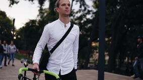 Σκεπτικός νέος επιχειρηματίας που περπατά με το ποδήλατο στην οδό στην πόλη Κύλισμα του ποδηλάτου οδοιπορίας του περπατώντας από  απόθεμα βίντεο