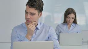 Σκεπτικός νέος επιχειρηματίας που σκέφτεται και που εργάζεται στο lap-top απόθεμα βίντεο
