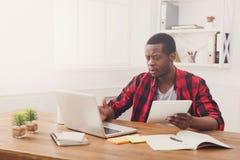 Σκεπτικός νέος μαύρος ευτυχής επιχειρηματίας στην αρχή, εργασία με το lap-top Στοκ φωτογραφία με δικαίωμα ελεύθερης χρήσης