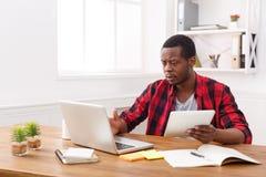 Σκεπτικός νέος μαύρος ευτυχής επιχειρηματίας στην αρχή, εργασία με το lap-top Στοκ εικόνα με δικαίωμα ελεύθερης χρήσης