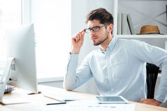Σκεπτικός νέος όμορφος επιχειρηματίας eyeglasses που εξετάζει το όργανο ελέγχου υπολογιστών Στοκ Εικόνα