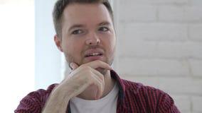 Σκεπτικός νεαρός άνδρας που σκέφτεται και που εργάζεται στο lap-top απόθεμα βίντεο