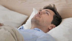 Σκεπτικός νεαρός άνδρας που σκέφτεται στο κρεβάτι φιλμ μικρού μήκους