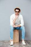Σκεπτικός νεαρός άνδρας στα γυαλιά ηλίου που κάθονται και που σκέφτονται Στοκ Εικόνες