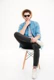 Σκεπτικός νεαρός άνδρας στο καπέλο και γυαλιά ηλίου που κάθονται στην καρέκλα Στοκ εικόνες με δικαίωμα ελεύθερης χρήσης