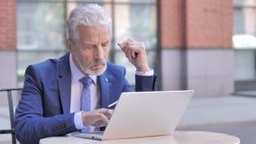 Σκεπτικός παλαιός επιχειρηματίας που χρησιμοποιεί το lap-top, υπαίθριο φιλμ μικρού μήκους