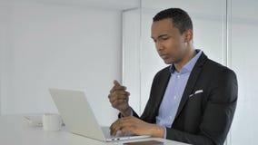 Σκεπτικός περιστασιακός αφροαμερικανός επιχειρηματίας που σκέφτεται και που εργάζεται στο lap-top φιλμ μικρού μήκους