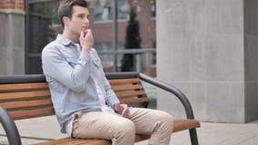 Σκεπτικός περιστασιακός νεαρός άνδρας που σκέφτεται καθμένος υπαίθριος απόθεμα βίντεο