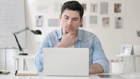 Σκεπτικός περιστασιακός νεαρός άνδρας που σκέφτεται στην εργασία απόθεμα βίντεο