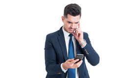 Σκεπτικός σοβαρός επιχειρηματίας που εξετάζει κάτω το κινητό τηλέφωνο Στοκ Εικόνες