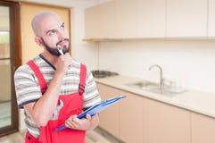 Σκεπτικός υδραυλικός στην κουζίνα Στοκ Φωτογραφία