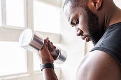 Σκεπτικός φίλαθλος αφρικανικός τύπος που εκπαιδεύει τους μυς σωμάτων του Στοκ Εικόνα
