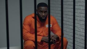 Σκεπτικός φυλακισμένος αφροαμερικάνων που περιμένει τους επισκέπτες, εξυπηρετώντας ισόβια φιλμ μικρού μήκους