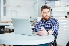 Σκεπτικό άτομο με το φορητό προσωπικό υπολογιστή στον καφέ Στοκ εικόνα με δικαίωμα ελεύθερης χρήσης