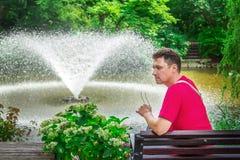 Σκεπτικό άτομο, που κάθεται σε έναν ξύλινο πάγκο Στοκ Εικόνες