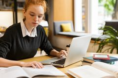 Σκεπτικό κοκκινομάλλες έφηβη που χρησιμοποιεί το φορητό προσωπικό υπολογιστή στοκ φωτογραφία με δικαίωμα ελεύθερης χρήσης