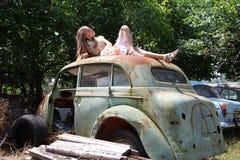 Σκεπτικό κορίτσι χωρών από ένα παλαιό σπασμένο αυτοκίνητο Στοκ Φωτογραφίες