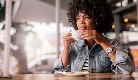 Σκεπτικό νέο θηλυκό που έχει τον καφέ σε ένα εστιατόριο Στοκ εικόνα με δικαίωμα ελεύθερης χρήσης