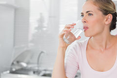 Σκεπτικό ξανθό πόσιμο νερό γυναικών Στοκ εικόνα με δικαίωμα ελεύθερης χρήσης