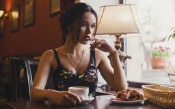 Σκεπτικό προκλητικό κορίτσι στο κάθισμα στη μετάβαση των καφέδων και καφές κατανάλωσης με το επιδόρπιο Στοκ φωτογραφίες με δικαίωμα ελεύθερης χρήσης