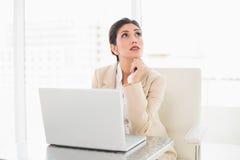 Σκεπτόμενη επιχειρηματίας που εργάζεται με ένα lap-top Στοκ Εικόνες