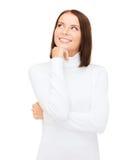 Σκεπτόμενη και χαμογελώντας γυναίκα στο άσπρο πουλόβερ Στοκ Φωτογραφίες