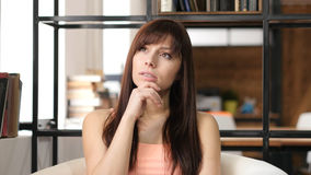 Σκεπτόμενη νέα γυναίκα, εσωτερικό γραφείο Στοκ εικόνες με δικαίωμα ελεύθερης χρήσης
