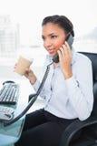 Σκεπτόμενη νέα μελαχροινή μαλλιαρή επιχειρηματίας που απαντά στο τηλέφωνο κρατώντας ένα φλιτζάνι του καφέ Στοκ φωτογραφία με δικαίωμα ελεύθερης χρήσης