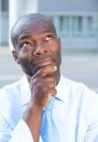 Σκεπτόμενος επιχειρηματίας από την Αφρική μπροστά από το γραφείο του Στοκ Εικόνα