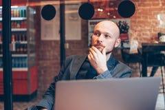 Σκεπτόμενο ελκυστικό ενήλικο επιτυχές φαλακρό γενειοφόρο άτομο στο κοστούμι με το lap-top στον καφέ στοκ εικόνα