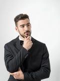 Σκεπτόμενο νέο γενειοφόρο άτομο στο σμόκιν με το δεσμό τόξων σχετικά με τη γενειάδα που κοιτάζει μακριά Στοκ εικόνα με δικαίωμα ελεύθερης χρήσης