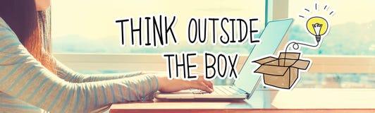 Σκεφτείτε έξω από το κιβώτιο με τη γυναίκα που εργάζεται σε ένα lap-top στοκ εικόνα