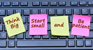 Σκεφτείτε ότι η μεγάλη έναρξη μικρή είναι υπομονετικές λέξεις στις σημειώσεις στοκ εικόνες