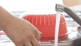 Σκεύος για την κουζίνα πλύσης γυναικών κάτω από το ρεύμα νερού φιλμ μικρού μήκους