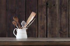 Σκεύος για την κουζίνα στο παλαιό ξύλινο υπόβαθρο στοκ φωτογραφίες