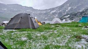 Σκηνές κατά τη διάρκεια του χαλαζιού και της κρύας βροχής το καλοκαίρι, μεσημβρία στη λίμνη Bucura, βουνά Retezat Άποψη από μέσα  στοκ φωτογραφία