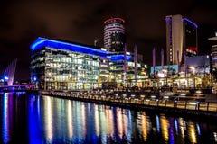 Σκηνές νύχτας με τα επιχειρησιακά γραφεία τη νύχτα με τις μακροχρόνιες αντανακλάσεις Στοκ Εικόνα