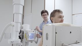 Σκηνή εξοπλισμού ακτινογραφιών στην κλινική με το άτομο στη roentgen μηχανή φιλμ μικρού μήκους
