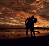 Σκηνή ζεύγους του ηλιοβασιλέματος αγάπης στην παραλία Στοκ Εικόνες