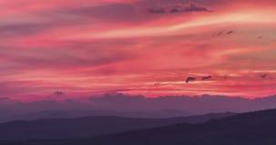 Σκηνή ηλιοβασιλέματος με την πτώση ήλιων πίσω από τα σύννεφα και τα βουνά στο υπόβαθρο, χρονικό σφάλμα πυροβοληθε'ν, θερμός ζωηρό απόθεμα βίντεο