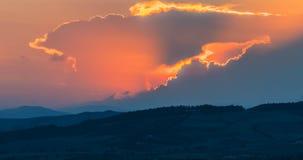 Σκηνή ηλιοβασιλέματος με την πτώση ήλιων πίσω από τα σύννεφα και τα βουνά στο υπόβαθρο, θερμός ζωηρόχρωμος ουρανός με φιλμ μικρού μήκους