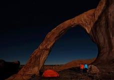 Σκηνή και παντρεμένο ζευγάρι στρατοπέδευσης που απολαμβάνουν τη θέα της φυσικών αψίδας και των αστεριών τη νύχτα στοκ φωτογραφίες