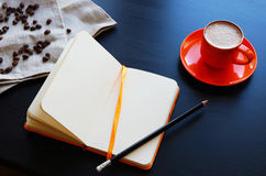 Σκηνή με το πορτοκαλί σημειωματάριο, τον καφέ espresso και τα φασόλια καφέ Στοκ Φωτογραφίες