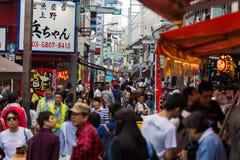 Σκηνή οδών του Τόκιο που παρουσιάζει αγοραστές κάτω από τον υπόγειο στοκ φωτογραφία