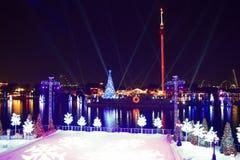 Σκηνή πατινάζ πάγου, ζωηρόχρωμα δέντρα διακοπών και χριστουγεννιάτικο δέντρο στη λίμνη και υπόβαθρο πύργων ουρανού στη διεθνή περ στοκ φωτογραφία με δικαίωμα ελεύθερης χρήσης