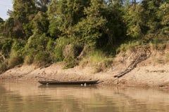 Σκηνή ποταμών του ξύλινου κανό που δένεται στο riverbank στοκ εικόνες