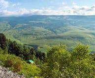 Σκηνή τουριστών στο στρατόπεδο μεταξύ του λιβαδιού στο βουνό Στοκ Εικόνες