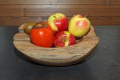 Σκηνή των φρούτων σε ένα ξύλινο κύπελλο στο σκοτεινό πίνακα στοκ φωτογραφία