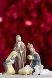 Σκηνή Nativity στο κόκκινο υπόβαθρο με τη διαστημική κατακόρυφο αντιγράφων Στοκ φωτογραφία με δικαίωμα ελεύθερης χρήσης